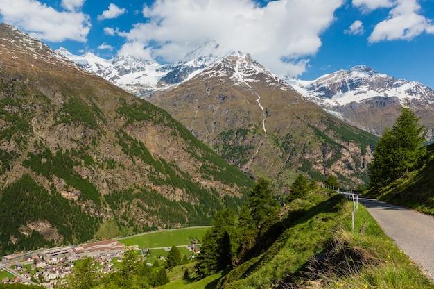 Paesaggio di montagna delle alpi estive con foresta di abeti sul pendio e cime rocciose coperte di neve in lontananza, svizzera