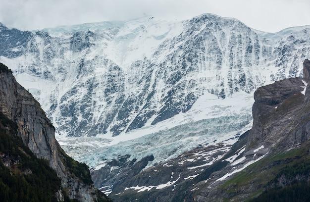 Paesaggio montano estivo delle alpi con ghiacciaio e cime rocciose coperte di neve in lontananza, svizzera