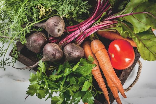 Estate, vendemmia autunnale. verdure biologiche fresche dell'azienda agricola in una scatola di legno sulle barbabietole di una tavola di marmo bianche, carote, prezzemolo, pomodori. vista dall'alto