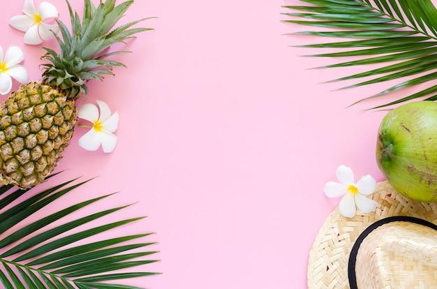 Concetto di sfondo estivo con cappello da spiaggia, cocco, ananas e fiori di frangipani su sfondo rosa