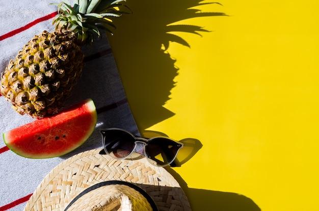 Concetto di sfondo estivo con occhiali da sole, cappello da spiaggia, fetta di anguria e ananas su telo da spiaggia con sfondo giallo e ombra dalla luce solare