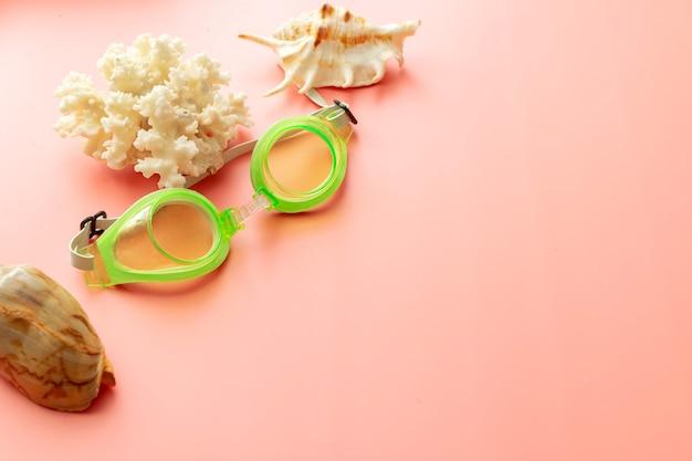 Sfondo estivo di corallo, occhialini da nuoto, sfondo rosa shellson