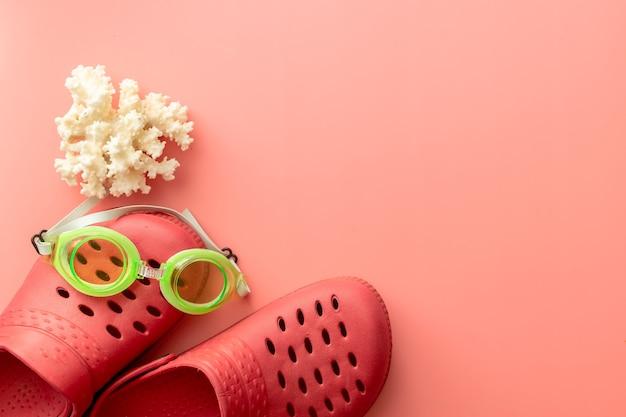 Sfondo estivo di coccodrilli, corallo, occhialini da nuoto, su sfondo rosa