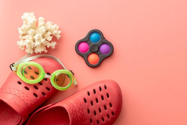 Sfondo estivo di coccodrilli, occhialini da nuoto, conchiglie, pop-it su sfondo rosa