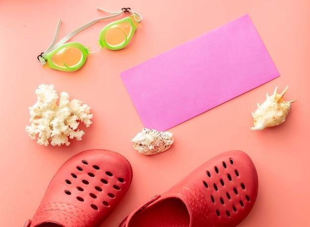 Sfondo estivo di coccodrilli, busta non stampata, occhialini da nuoto, conchiglie, corallo su sfondo rosa