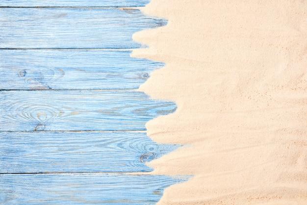 Sfondo estivo da sabbia di mare e assi di legno blu