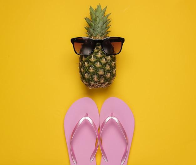 Sfondo estivo. divertimento e umorismo. il concetto di una vacanza al mare. ananas con occhiali da sole, infradito