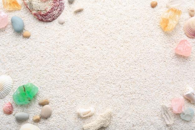 Fondo di estate delle conchiglie e dei ciottoli del mare sulla sabbia della spiaggia.