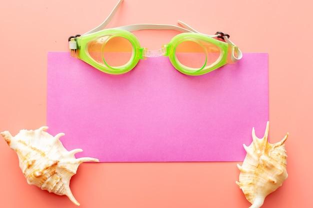 Sfondo estivo di conchiglie, occhialini da nuoto e busta estiva su sfondo rosa