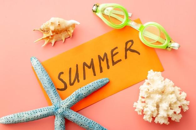 Sfondo estivo di stelle marine, conchiglie, occhialini da nuoto e busta estiva su sfondo rosa