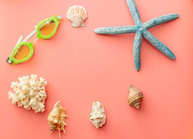Sfondo estivo di stelle marine, occhialini da nuoto, conchiglie, corallo su sfondo rosa