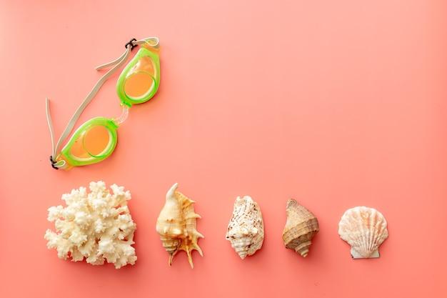 Sfondo estivo di occhialini da nuoto, conchiglie, corallo su sfondo rosa
