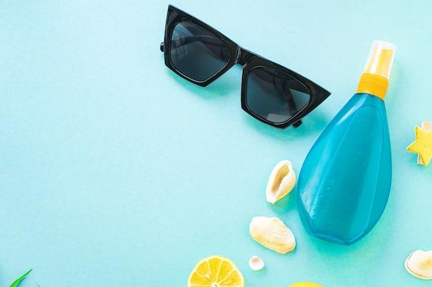 Sfondo estivo accessori da viaggio oceano mare crema solare bottiglia di lozione occhiali da sole conchiglie limone