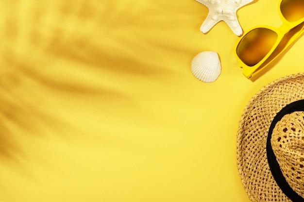 Sfondo estivo con ombre di foglie. cappello di paglia, occhiali da sole, conchiglia e stelle marine su superficie gialla. spazio vuoto della copia. viaggiare e concetto di ora legale.