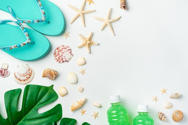 Sfondo estivo con stelle marine, vongole, infradito, foglie di monstera e una bevanda in bottiglia su uno sfondo chiaro.