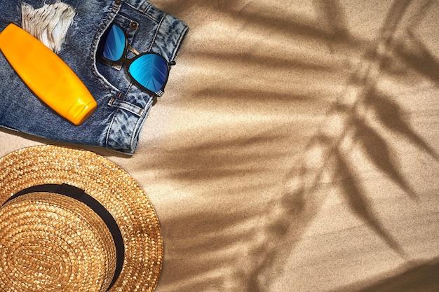 Sfondo estivo con cappello di paglia, occhiali da sole, bottiglia di crema solare e infradito