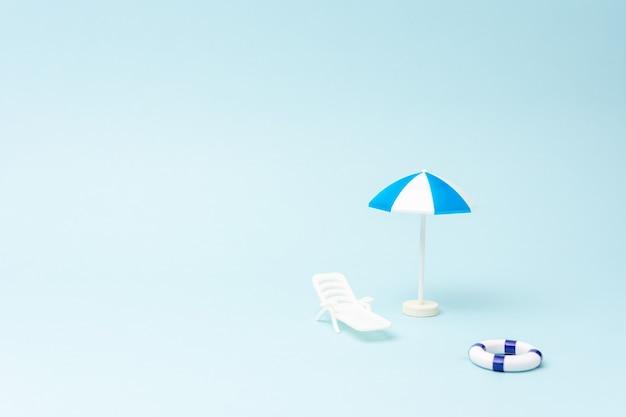 Sfondo estivo con lettino ombrellone e anello per nuotare su sfondo blu pastello