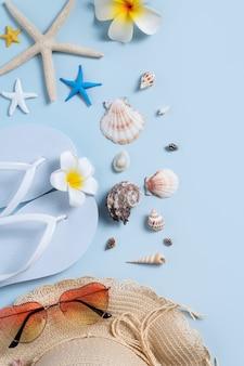 Concetto di design del fondo della spiaggia di estate. vista dall'alto del viaggio di vacanza con conchiglie, cappello, pantofola su sfondo blu.
