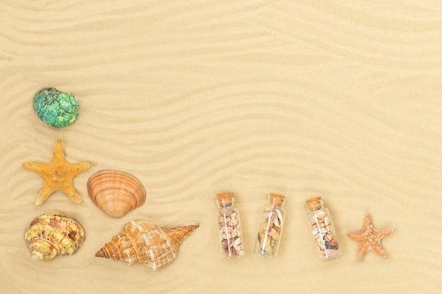 Fondo della spiaggia di estate con le stelle marine delle conchiglie e le piccole bottiglie sulla sabbia