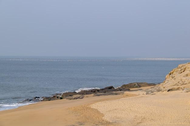 Spiaggia estiva, cielo azzurro, spiaggia dorata e piccole onde