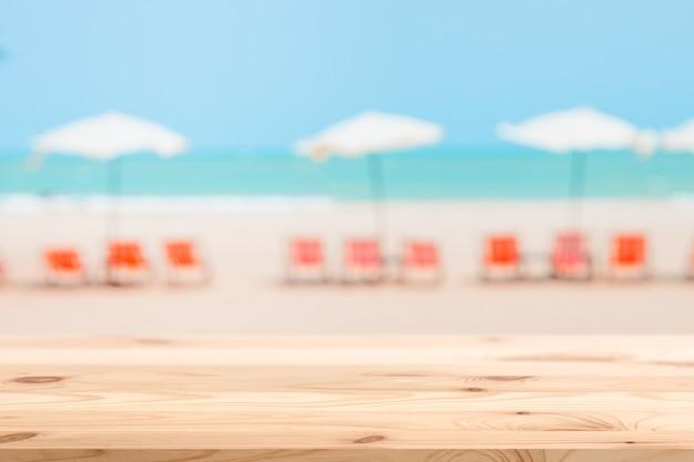 Sfocatura dell'ombrellone della sedia da spiaggia estiva con piano del tavolo in legno per lo spazio pubblicitario di sfondo dei prodotti di montaggio