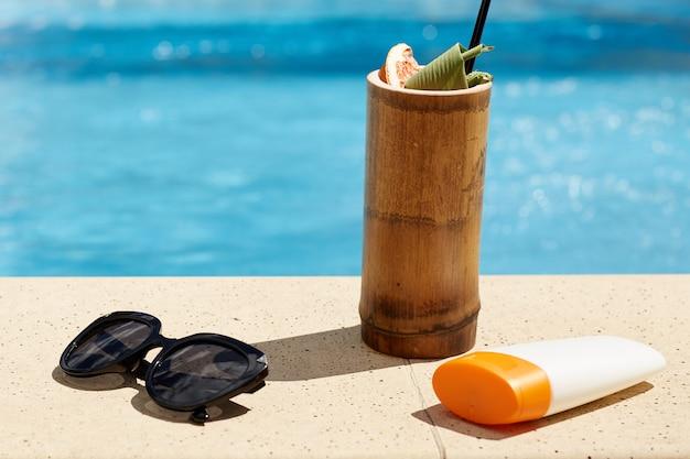 La spiaggia dell'estate ha messo sull'acqua della piscina, sugli occhiali da sole neri, sulla protezione solare e sul cocktail saporito in vetro di legno, le cose della donna alla piscina del pilastro nel ricorso di stazione termale.