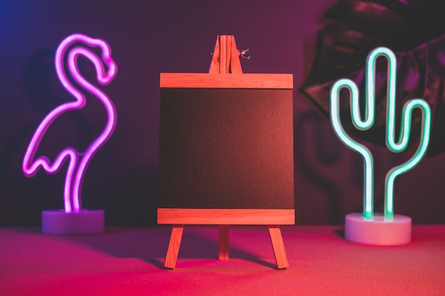 Lavagna estate con luce al neon rosa e blu flamingo e cactus sul tavolo