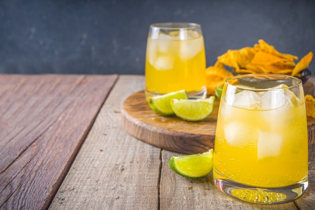 Cocktail estivo alcolico agli agrumi, margarita agli agrumi, tequila con sale e patatine messicane