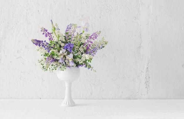 Bouquet estivo in vaso bianco su sfondo bianco