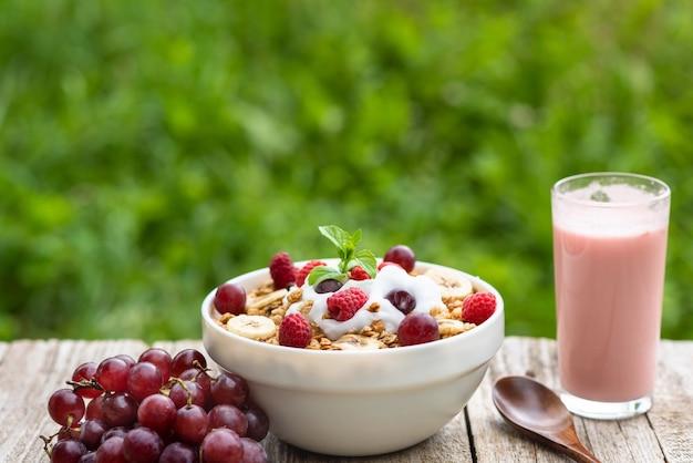 Colazione estiva di cereali con uva, latte e yogurt ai frutti di bosco all'aperto nella natura. vegetariana colazione mattutina sullo sfondo di erba verde. copia spazio.