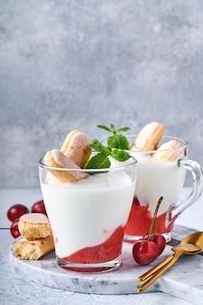 Sfogliatina estiva alle ciliegie con savoiardi e crema di formaggio in vetro su fondo grigio chiaro. torta tiramisù tradizionale con frutti di bosco freschi. messa a fuoco selettiva.