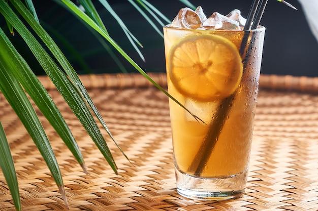 Bevande estive fresche con succo d'arancia fresco e cola sul tavolo di vimini con foglie