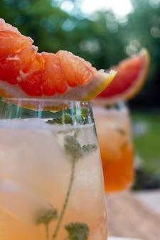 Cocktail estivo con fiori di pompelmo e ghiaccio