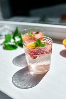 Cocktail estivo con fragole, arancia e menta in vetro sul tavolo bianco