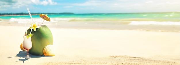 Cocktail estivo di cocco sulla spiaggia. giornata di sole nell'isola d'attualità.