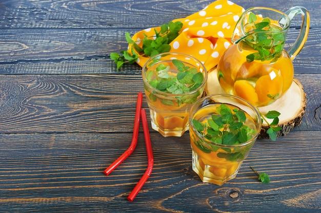Bevande fredde estive. composta di frutta. bevanda rinfrescante deliziosa con l'albicocca e la menta in vetro su una tavola di legno.