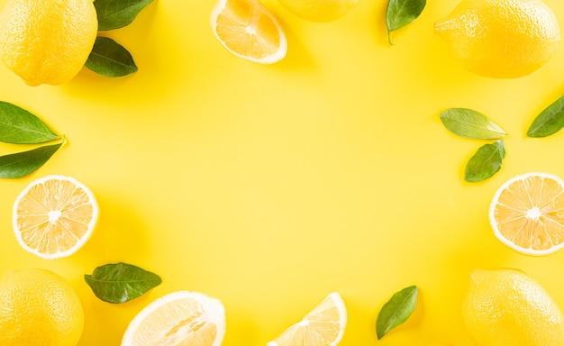 Composizione estiva a base di arance, limone e foglie verdi su sfondo giallo pastello frutta concetto minimo fruit