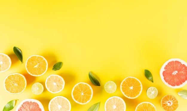 Composizione estiva a base di arance, limone o lime su sfondo giallo pastello concetto minimo di frutta