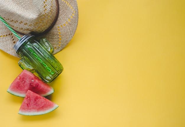 Composizione estiva con anguria, cappello e contenitore per succhi di frutta su sfondo giallo. concetto di estate. copia spazio. disteso.