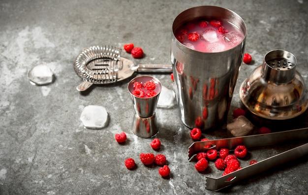 Cocktail estivo rinfrescante di lamponi selvatici con ghiaccio. sul tavolo di pietra.