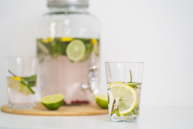 Bevanda rinfrescante estiva con frutti di bosco e limonata agli agrumi in una bottiglia di vetro riutilizzabile