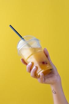 Bevanda estiva limonata fresca con arancia nel bicchiere di plastica su sfondo giallo. mano femminile che tiene un bicchiere. mockup per la tua pubblicità. copia spazio.