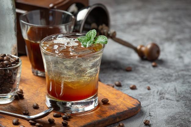 Bevanda estiva caffè ghiacciato o soda in un bicchiere sulla superficie scura.