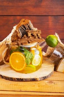 Bevanda estiva di foglie di acqua, limone, arancia e menta su tavole di legno. tè freddo alla menta lime e pezzi di legno. composizione creativa