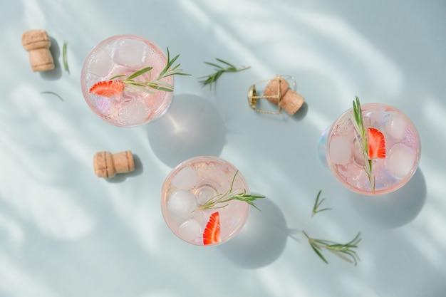 Bevanda estiva con spumante bianco. cocktail di frutta rinfrescante fatto in casa o punch con champagne, fragole, cubetti di ghiaccio e rosmarino