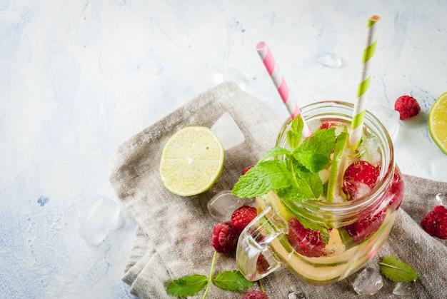 Bevande estive, cocktail. cibo vegano. acqua disintossicante infusa con lime, menta e lamponi freschi biologici