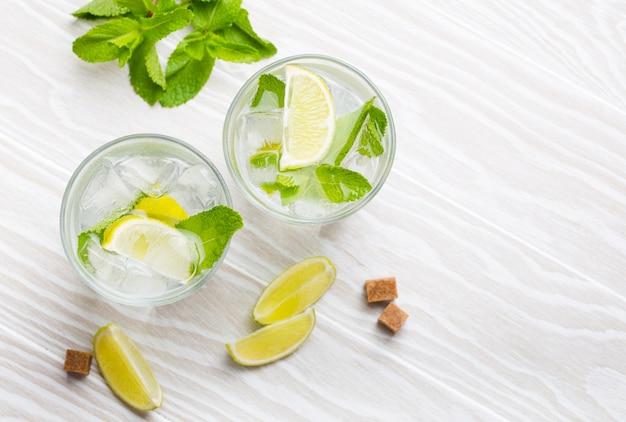 Bevande estive con ghiaccio, lime e menta fresca in bicchieri su fondo rustico in legno bianco. vista dall'alto di limonate/mojito rinfrescanti fredde, ideali per feste estive e divertimento, dall'alto, primo piano