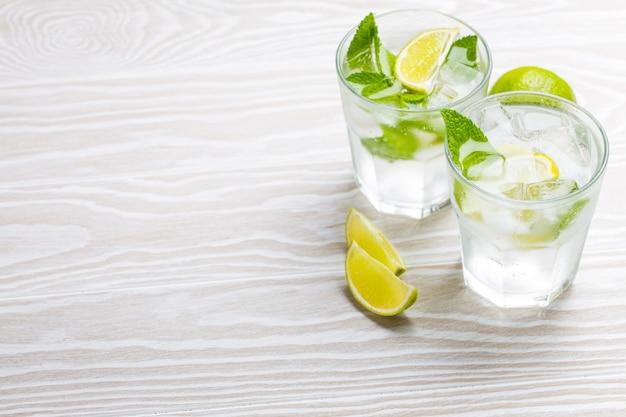 Bevande estive con ghiaccio, fette di lime, menta fresca in bicchieri su fondo rustico in legno bianco, spazio per il testo. limonate/mojito rinfrescanti fredde ottime per feste estive e divertimento, copia spazio, vista angolare