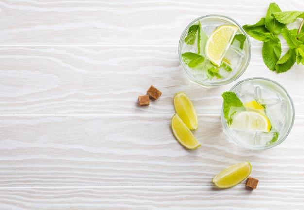 Bevande estive con ghiaccio, fette di lime, menta fresca in bicchieri su fondo rustico in legno bianco, spazio per il testo. limonate/mojito rinfrescanti fredde ottime per feste estive e divertimento, copia spazio, vista dall'alto