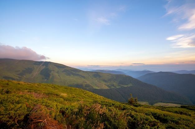 Paesaggio montano serale estivo con colline erbose e cime lontane al tramonto colorato.